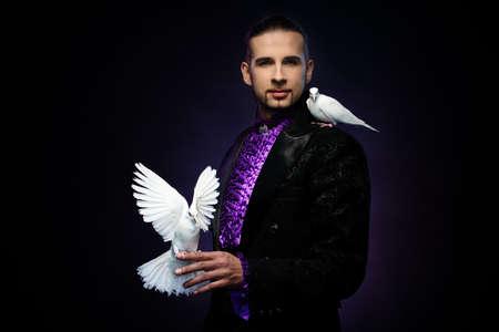 mago: Joven mago morena guapo en traje de la etapa con sus palomas blancas capacitados Foto de archivo