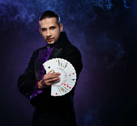 conjuror: Young brunette magician in stage costume showing card tricks  Stock Photo