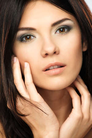 touching face: Young beautiful brunette woman with make-up  touching her face