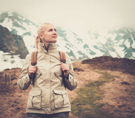 Young blond woman hiker walking in mountains photo
