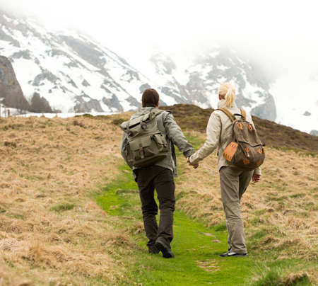 Couple of hikers with backpacks walking in the mountains photo