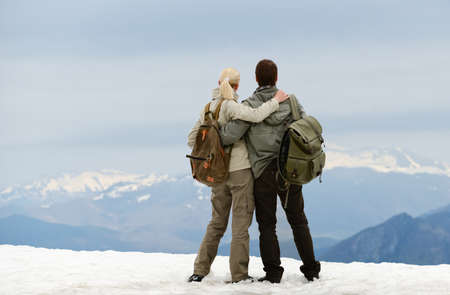 Couple of hikers with backpacks looking over mountains view photo