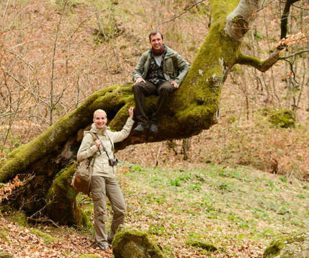 Happy smiling travellers couple in a forest photo