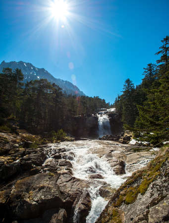 Fast river in mountain forest with little waterfall photo
