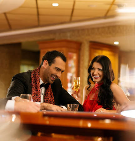 casino table: Happy young couple sitting with drinks behind table  Stock Photo