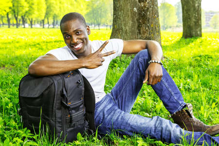 Young smiling african american man with rucksack in a park photo