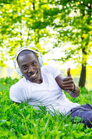 Smiling young african american man in white shirt listens music in a park photo