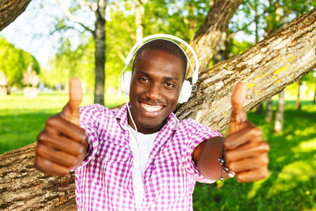 Young happy smiling african american listens to music in a park photo