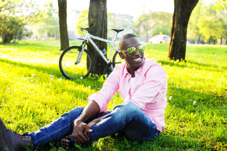 Young happy smiling african american wearing sunglasses with bicycle behind him in a park photo