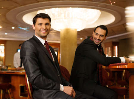 Two young men in suits behind table in a casino photo
