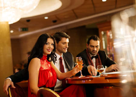 Young people in evening dress behind poker table in a casino photo