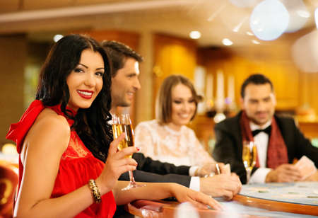 rijke vrouw: Groep jonge mensen het spelen van poker in een casino Stockfoto