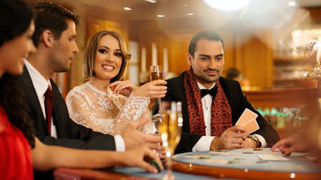 Group of young people playing poker in a casino photo