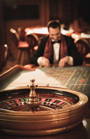 fichas casino: El hombre en traje y bufanda jugando a la ruleta en un casino Foto de archivo