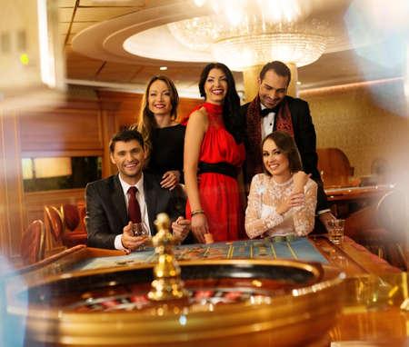 ruleta de casino: Grupo de jóvenes detrás de la mesa de ruleta en un casino Foto de archivo