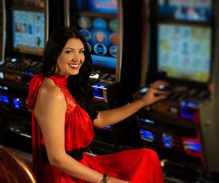 スロット マシンを再生する赤いドレスで美しい女性