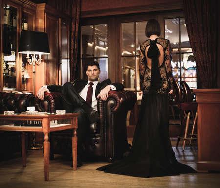 donna ricca: Coppia elegante in abito formale in cabinet di lusso