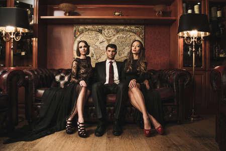 2 つの美しい女性とソファの上に座ってのスーツを着てハンサムなブルネット