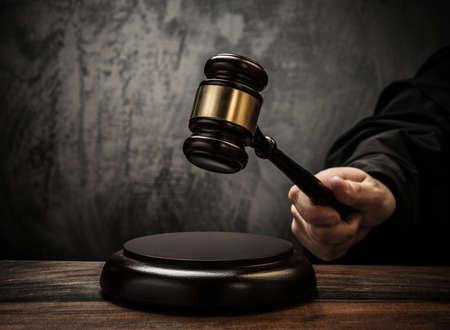 裁判官の木製のテーブルの上のハンマーを保持します。