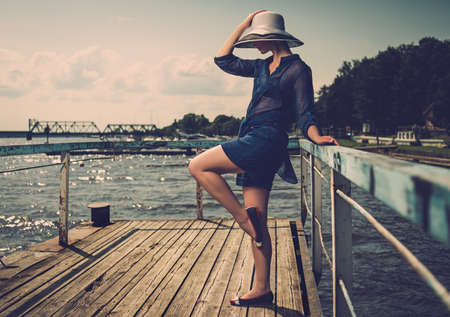Stylish woman in white hat standing on old wooden pier  photo