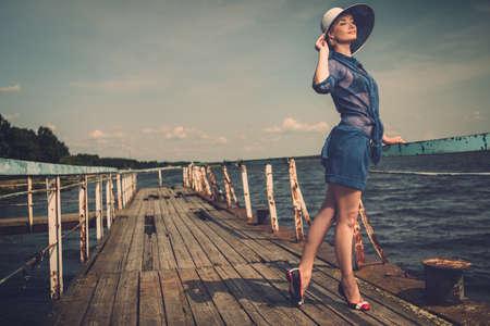 Stijlvolle vrouw in witte hoed die zich op oude houten pier Stockfoto