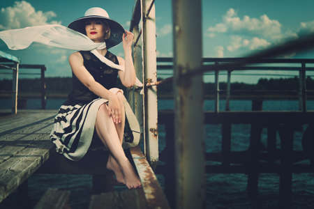 old pier: Beautiful woman wearing hat and white scarf sitting on old wooden pier  Stock Photo