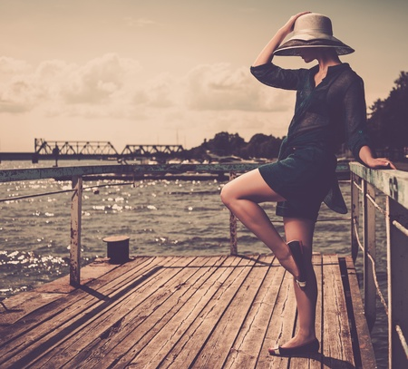 Stylish woman in white hat standing on old wooden pier