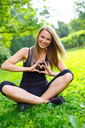 Giovane ragazza felice sportiva che mostra il segno del cuore con le sue mani su un prato in un parco Archivio Fotografico - 20824001