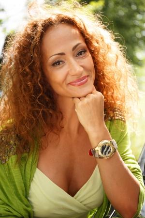 Prachtige middelbare leeftijd roodharige glimlachende vrouw in openlucht