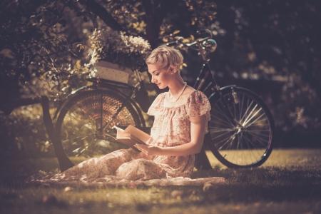 금발의 아름 다운 레트로 여자는 풀밭에 책을 읽고