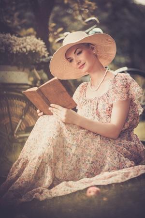 Blond beautiful retro woman reading book on a meadow  Zdjęcie Seryjne
