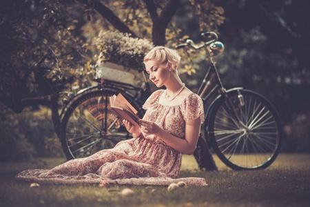 Blond beautiful retro woman reading book on a meadow Standard-Bild