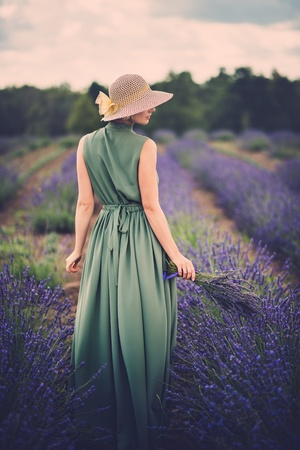 Woman in long green dress and hat in a lavender field Stock Photo