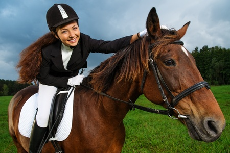 Beautiful smiling girl sitting on a horse outdoors  Stock Photo
