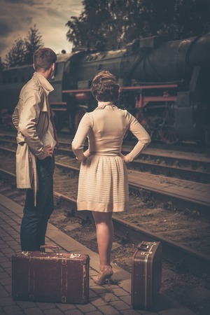 鉄道駅プラットフォームのスーツケースと美しいビンテージ スタイルのカップル