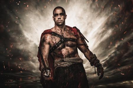 Blessé gladiateur avec l'épée contre le ciel orageux Banque d'images - 22368727