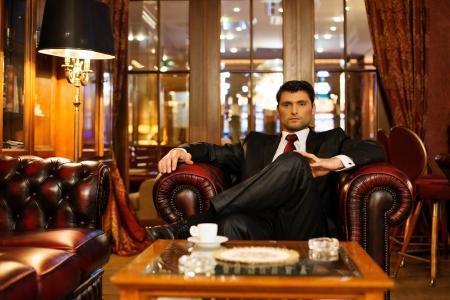 Zuversichtlich, gut aussehend Brünette sitzt im Luxus-Interieur