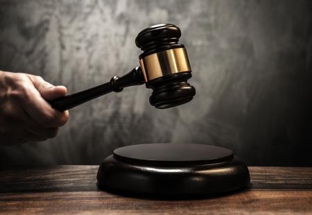 裁判官の保持の木製のハンマー 写真素材
