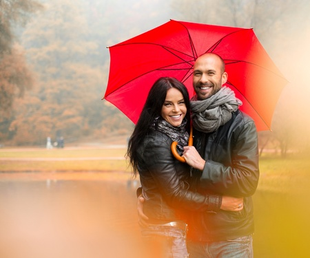 Happy middle-aged couple with umbrella outdoors on beautiful rainy autumn day   版權商用圖片