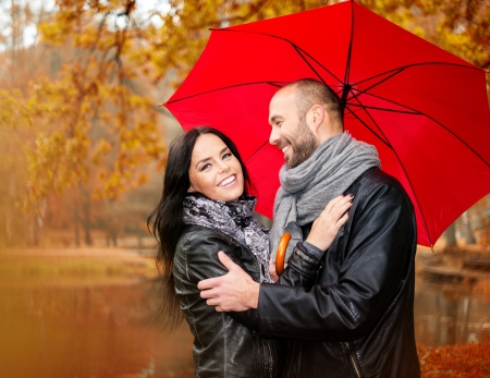 Happy middle-aged couple with umbrella outdoors on beautiful rainy autumn day   Stock Photo