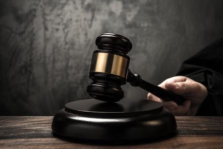 Judges hand holding wooden hammer  Stok Fotoğraf