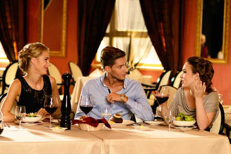 Young friends with glasses of red wine having conversation in a luxury restaurant  Stock Photo