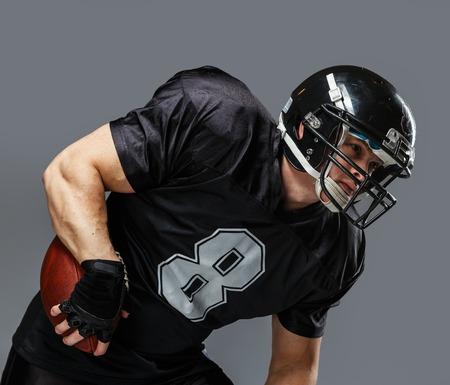 Joueur de football américain avec la bille de porter le casque et le maillot