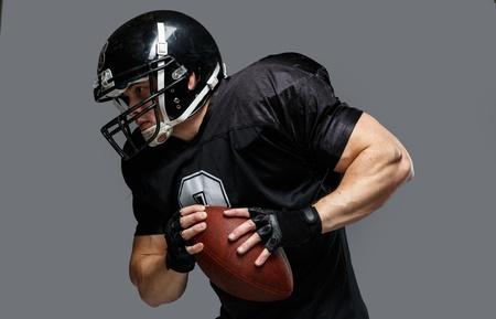 헬멧과 저지를 착용하는 공을 가진 미식 축구 선수
