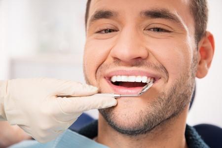 Hombre sonriente hermoso en el que hace chequeo en la consulta del dentista Foto de archivo