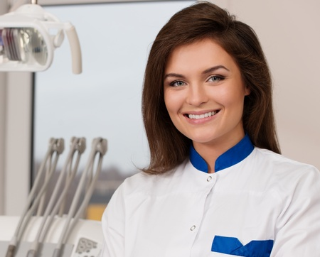 Young beautiful brunette female dentist at dentists surgery  Stock Photo