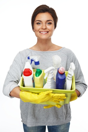 Beautiful cheerful brunette woman in gloves holding different cleaning stuff