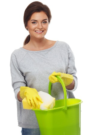 Beautiful cheerful brunette woman in gloves with sponge and bucket