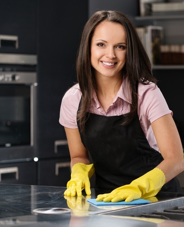 Beautiful cheerful brunette woman in gloves cleaning modern kitchen Stock Photo