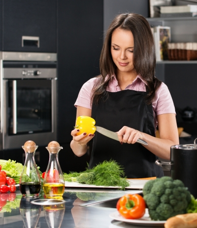 Cheerful young woman in apron on modern kitchen cutting vegetables Stock Photo